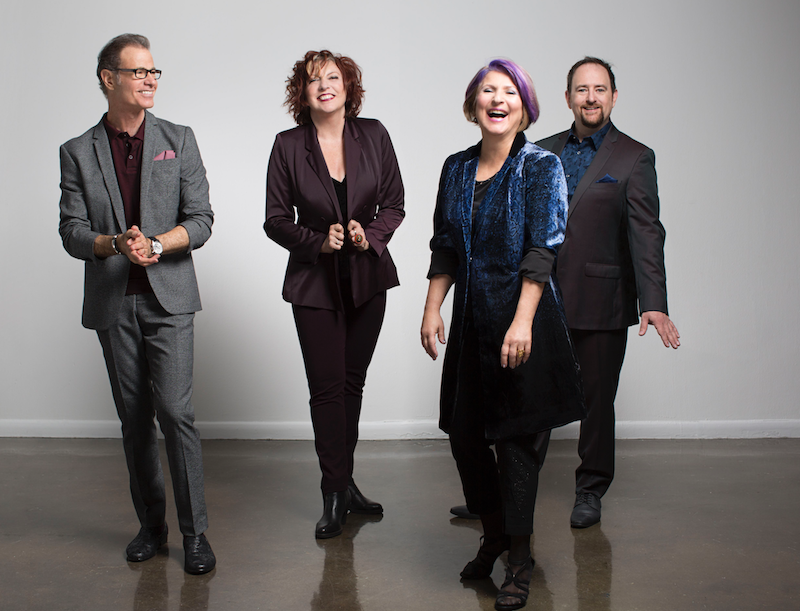 The four members of the Manhattan Transfer standing, smiling and laughing.