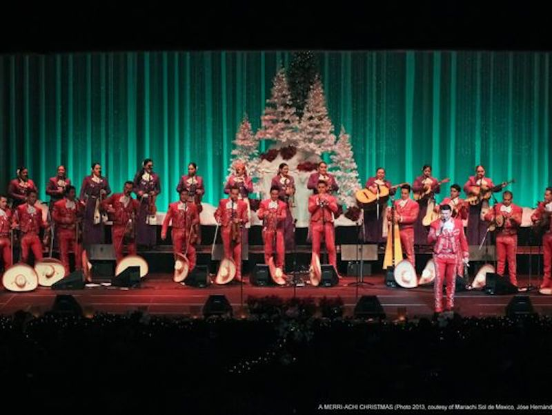 Mariachi Sol de Mexico performing on stage with Christmas trees in the baackground.