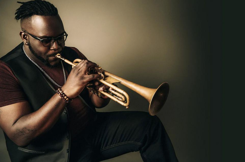 A photo of Marquis Hill playing the trumpet.