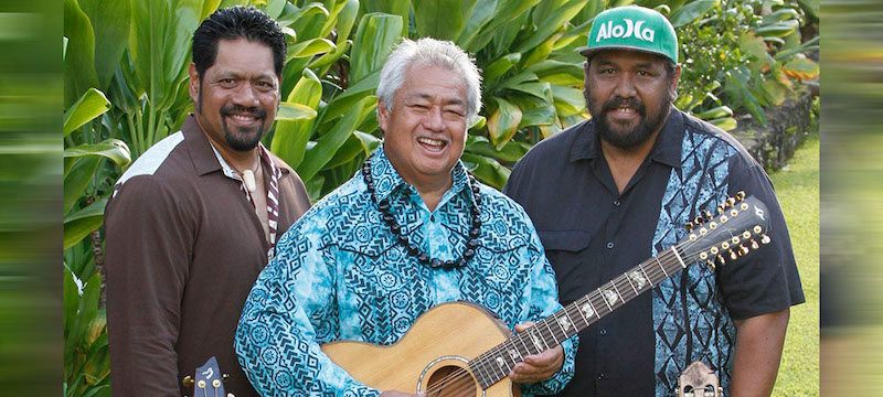 "George Kahumoku Jr., Nathan Aweau and David ""Kawika"" Kahiapo standing in front of green Hawaiian foliage."