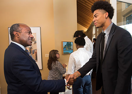 UC Davis Chancellor-designate welcomes a male student to the Chancellor's Residence