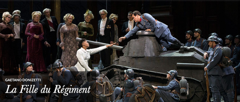 The company performing the opera on stage with a tank.