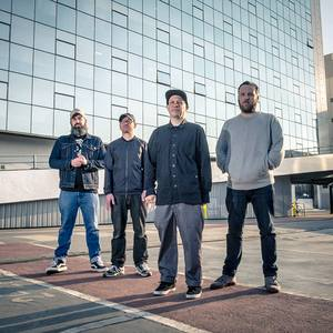 A photo of the band standing in front of a modern glass-sheathed building.