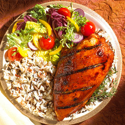 A plate with chicken, rice and a salad