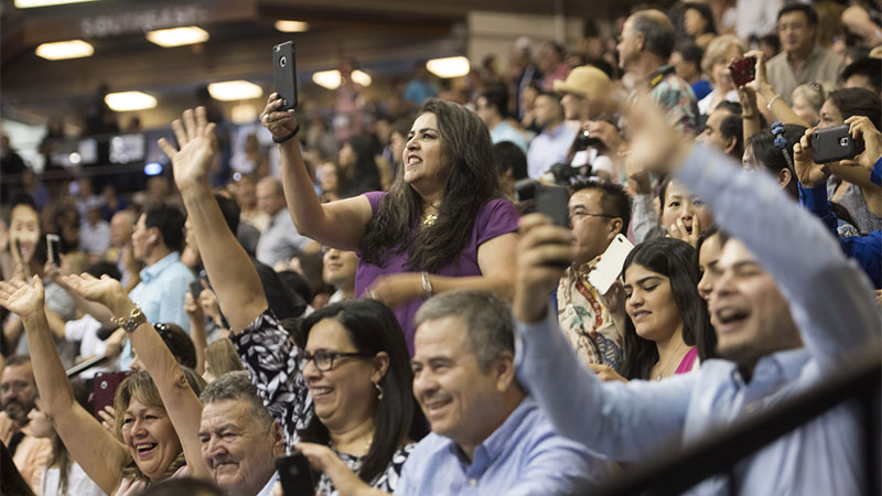 Family members cheer at a commencement ceremony.