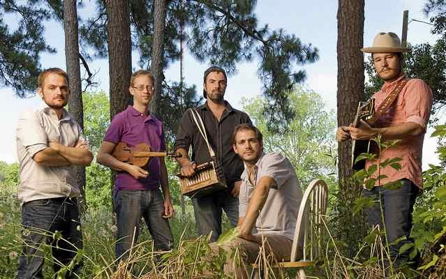 A photo of members of the band holding musical instruments and stading among trees.