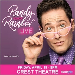 Randy Rainbow holding his pink frame reading glasses on the tip of his nose.