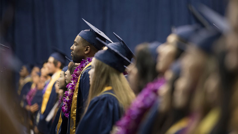 Students stand during an undergraduate commencement ceremony. (Credit?/UC Davis)