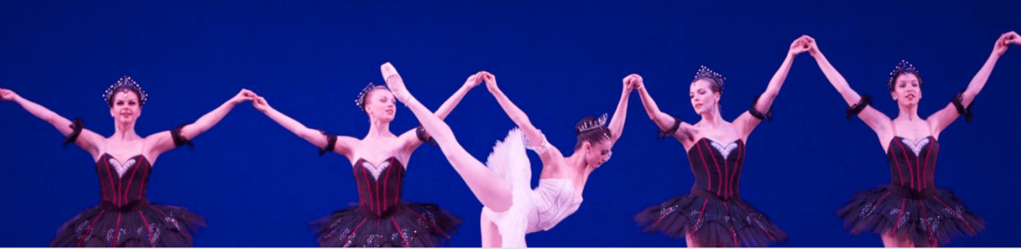 A photo of a prima ballerina backed by four other ballerinas.