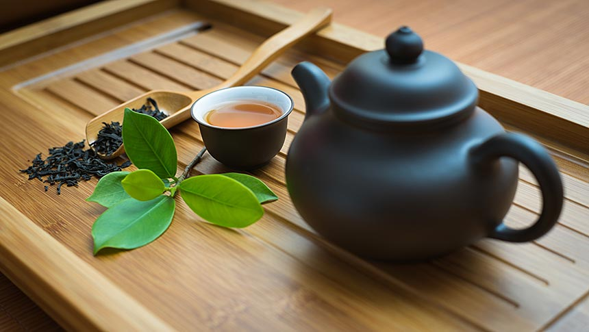 Bamboo tray holds tea leaves and teapot