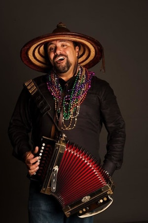 A photo of Terrance Simien holding an accordion.