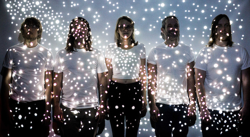 The members of the Deer photographed in dim light with tiny dots of light projected on them.