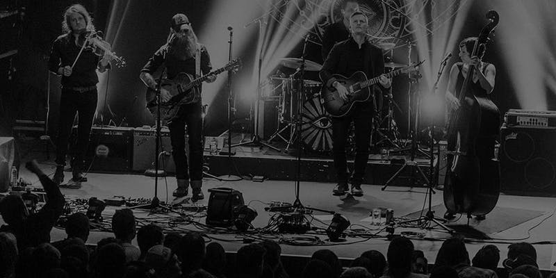 Black and white photo of members of the band performing on stage.