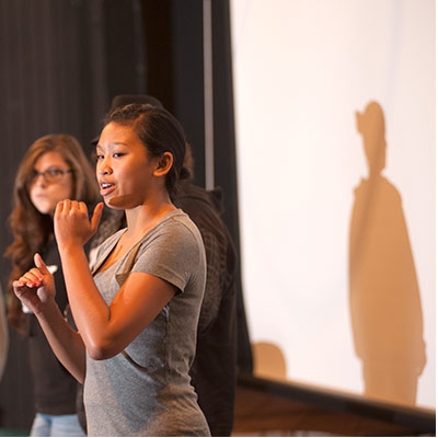 woman talking on stage with her shadow on the screen behind