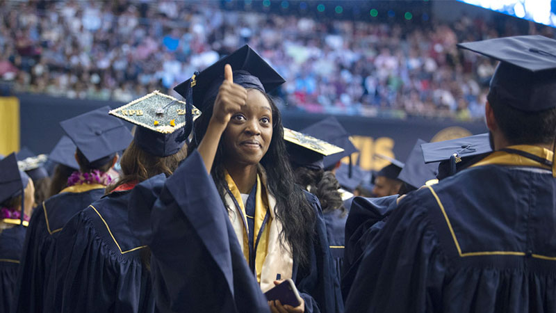 A female graduate gives a thumbs up at commencement