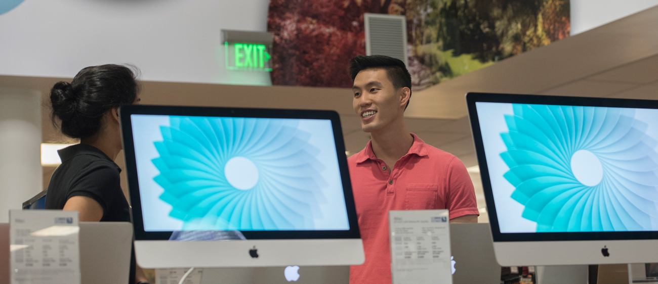 A UC Davis Stores worker consults with a customer in the tech section of the store.