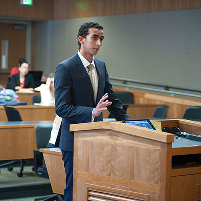 A law student stands at a podium to deliver his argument