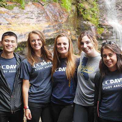 A group of Study Abroad students poses in front of a waterfall