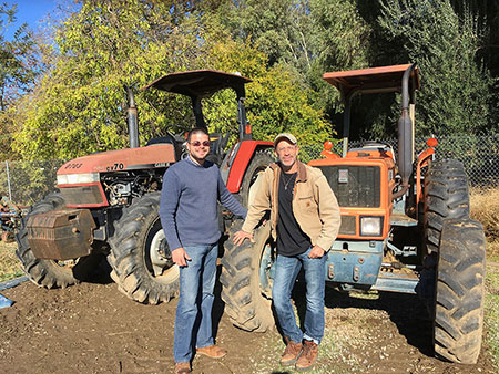 Two men in front of tractors