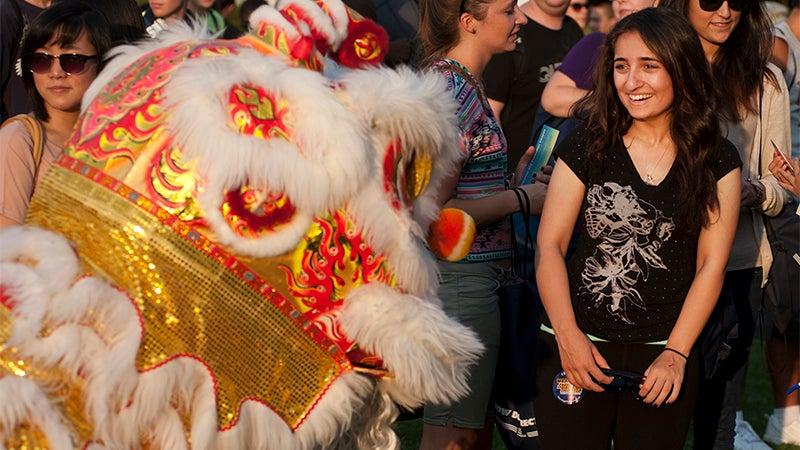 A lion dancer surprises a student