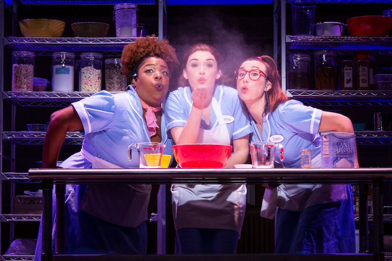 Three waitresses standing at a table, making a pie and blowing a handful of flour in the air.