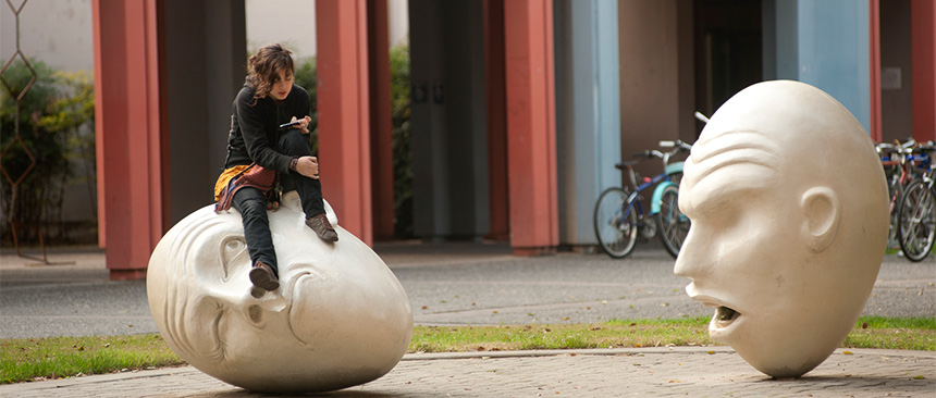 """Photo of woman sitting on top of one of two sculptures that comprise the """"Yin & Yang"""" Eggheads"""